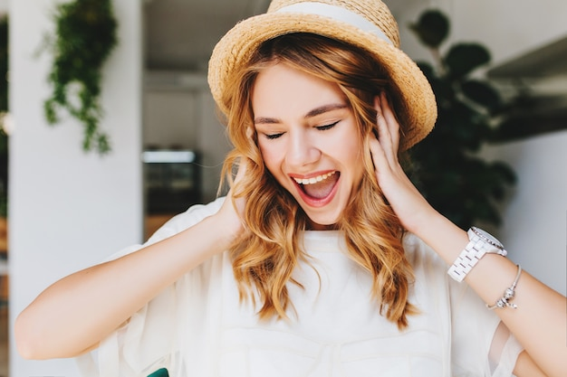 Nahaufnahmeporträt des ekstatischen lockigen mädchens trägt trendiges armband und armbanduhr, die mit geschlossenen augen lachen