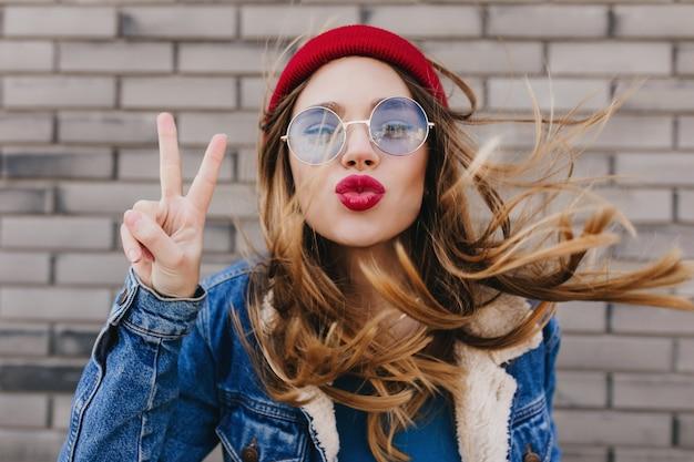 Nahaufnahmeporträt des ekstatischen weißen mädchens, das frühlingstag im freien verbringt. foto der inspirierten blonden frau trägt jeansjacke und roten hut, der mit küssendem gesichtsausdruck aufwirft.