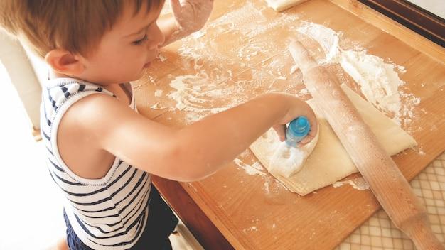 Nahaufnahmeporträt des entzückenden 3 jahre alten kleinkindjungen, der kekse backt und teig mit hölzernem roolingstift rollt. kleiner koch koch