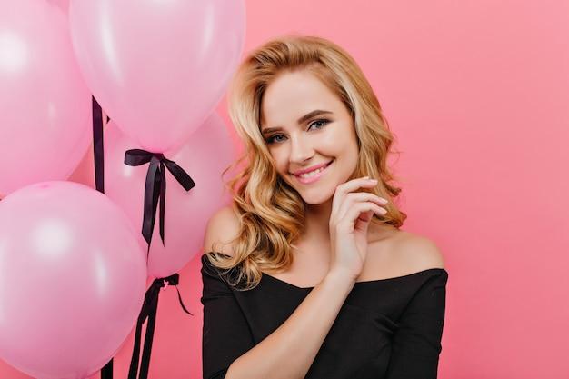 Nahaufnahmeporträt des entzückenden blonden geburtstagsmädchens. fröhliche blonde dame in schwarz posiert mit partyballons.