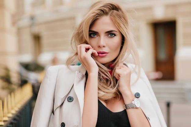 Nahaufnahmeporträt des entzückenden blonden mädchens mit rosa lippenstift, der spielerisch auf unscharfem straßenhintergrund aufwirft