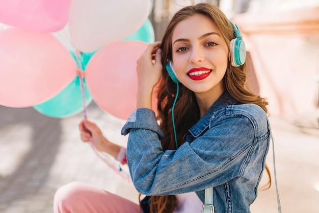 Nahaufnahmeporträt des entzückenden lächelnden mädchens, das jeansjacke trägt, die spaß an der geburtstagsfeier hat.
