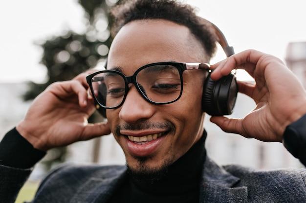 Nahaufnahmeporträt des entzückenden männlichen modells in der lässigen brille, die mit musik im park kühlt. foto des hübschen afrikanischen kerls mit dem dunklen haar, das in den kopfhörern aufwirft