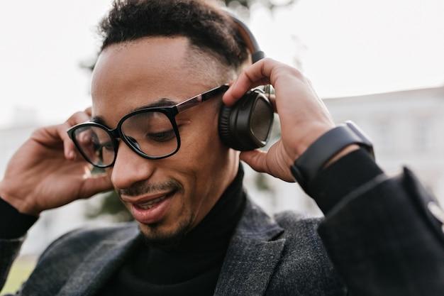 Nahaufnahmeporträt des entzückenden schwarzen mannes mit stilvollem haarschnitt, der musik mit geschlossenen augen hört. foto des müden afrikanischen kerls in den gläsern, die lied in kopfhörern genießen.