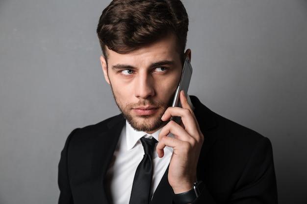 Nahaufnahmeporträt des ernsten jungen attraktiven mannes im schwarzen anzug, der auf handy spricht und beiseite schaut