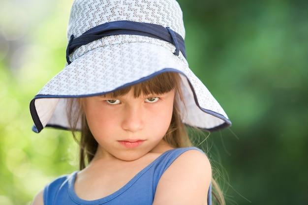 Nahaufnahmeporträt des ernsten kleinen mädchens in einem großen hut. kind, das spaßzeit draußen im sommer hat.