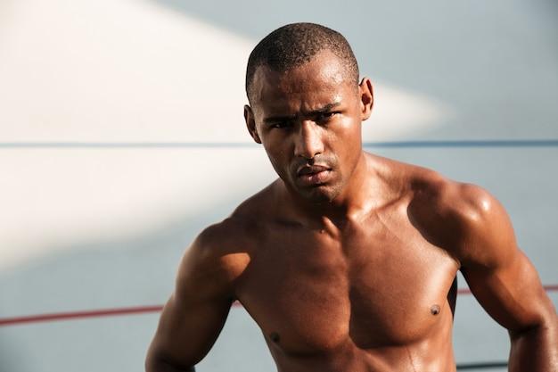 Nahaufnahmeporträt des ernsten müden gutaussehenden afroamerikanischen sportmannes, der nach dem training auf stadion ruht