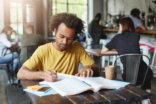 Nahaufnahmeporträt des ernsthaften dunkelhäutigen männlichen studenten, der gelbes t-shirt sitzt, das während der pause im café sitzt, kaffee trinkt und sich auf lektionen vorbereitet, die in heft aus buch mit bleistift schreiben