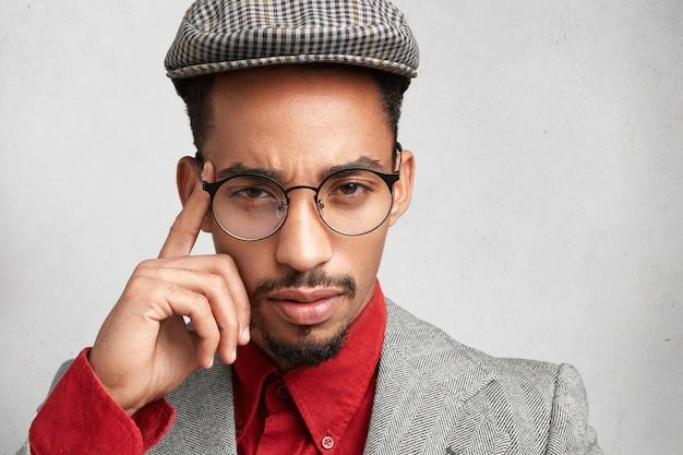 Nahaufnahmeporträt des ernsthaften dunkelhäutigen männlichen unternehmers trägt trendige mütze