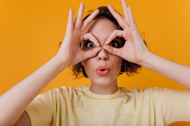 Nahaufnahmeporträt des erstaunlichen blassen mädchens, das lustige gesichter auf gelber wand macht. foto der lustigen weißen frau mit kurzem haarschnitt herumalbern.