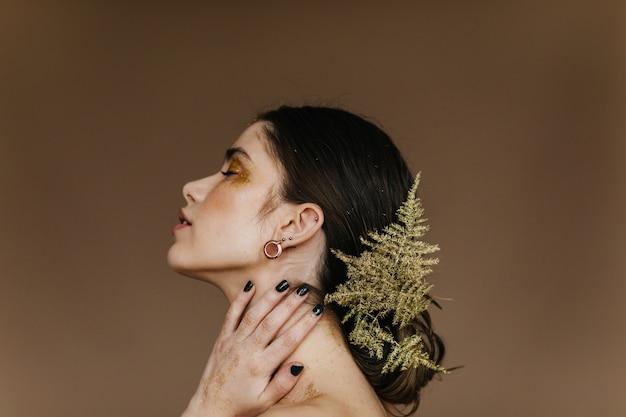 Nahaufnahmeporträt des erstaunlichen brünetten mädchens. attraktive kaukasische frau, die mit pflanze im haar aufwirft.