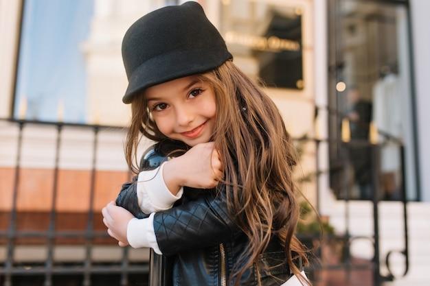Nahaufnahmeporträt des erstaunlichen langhaarigen kindes mit wundervollem freundlichem lächeln, das draußen posiert und eiserne säule umarmt.