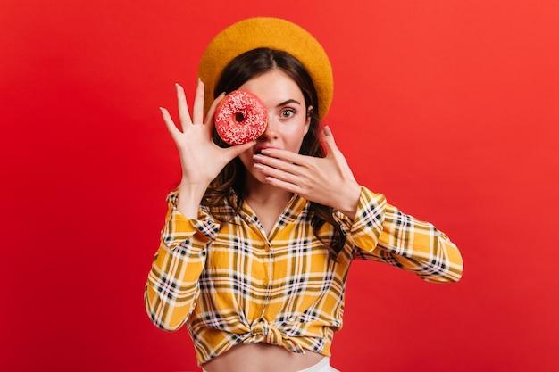 Nahaufnahmeporträt des erstaunten grünäugigen mädchens, das leckeren donut hält. dame in baskenmütze und hemd bedeckt ihren mund.