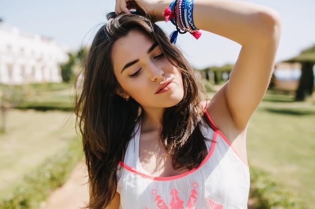 Nahaufnahmeporträt des faszinierenden brünetten mädchens in handgemachten accessoires, die draußen mit geschlossenen augen stehen. charmante junge frau mit dem schönen gesicht und den braunen haaren im weißen hemd, das aufwirft