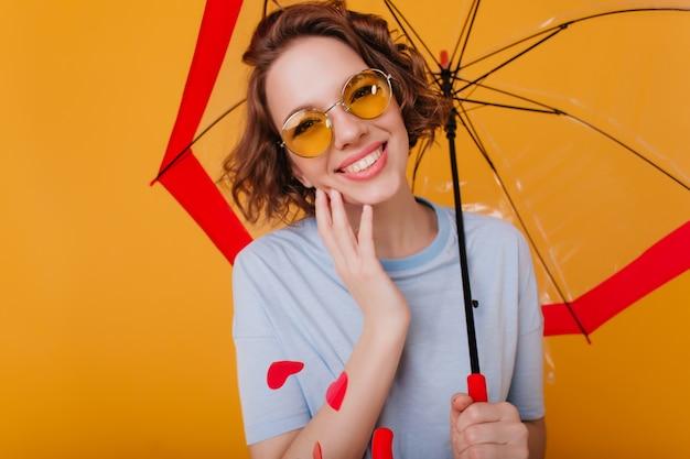 Nahaufnahmeporträt des freudigen braunhaarigen mädchens im t-shirt, das unter sonnenschirm aufwirft. lachende schöne dame in der sonnenbrille, die fotoshooting mit regenschirm genießt.