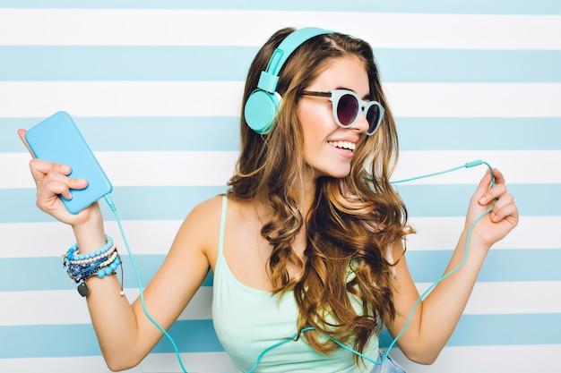 Nahaufnahmeporträt des freudigen mädchens, das musik in großen kopfhörern genießt und handy in der hand hält. attraktive junge frau, die schwarze sonnenbrille und trendige accessoires trägt, die auf gestreifter wand abkühlen.