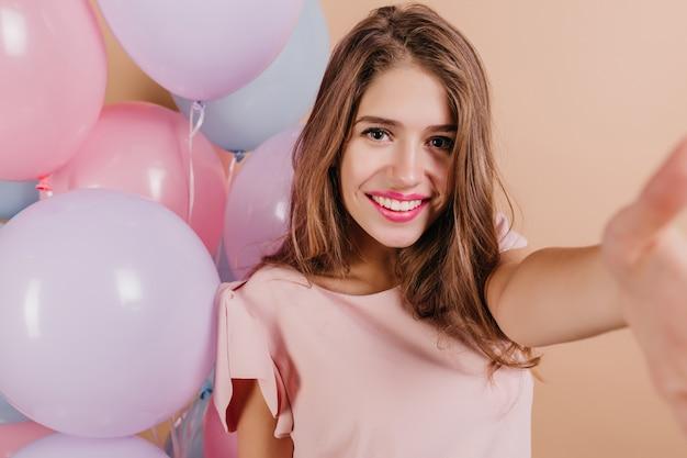 Nahaufnahmeporträt des freudigen weißen weiblichen modells mit hellem make-up, das geburtstagsfeier genießt