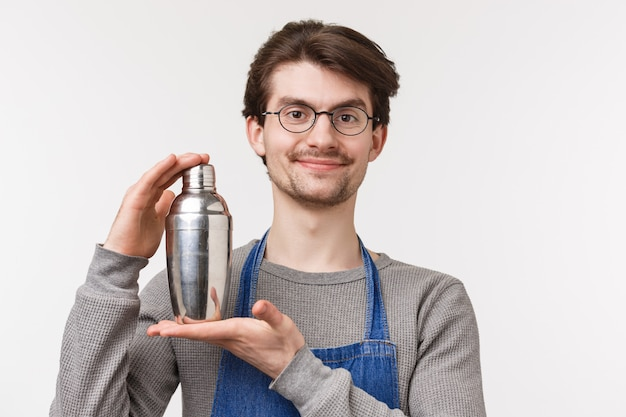 Nahaufnahmeporträt des fröhlich lächelnden jungen barkeepers, der daran arbeitet, einen neuen cocktail zu erfinden, getränk in shaker zu schütteln und kamera zu lächeln, getränk für kunden vorzubereiten,