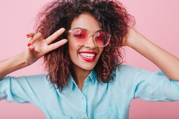 Nahaufnahmeporträt des fröhlichen afrikanischen mädchens, das wahres glück ausdrückt. hübsche mulattendame in der rosa brille, die friedenszeichen zeigt.
