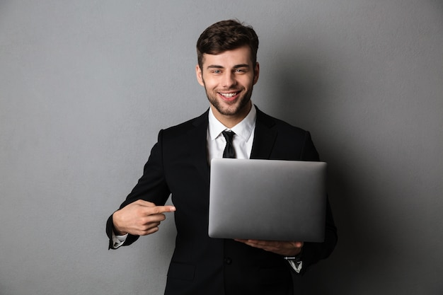 Nahaufnahmeporträt des fröhlichen geschäftsmannes, der mit finger auf seinem laptop zeigt,