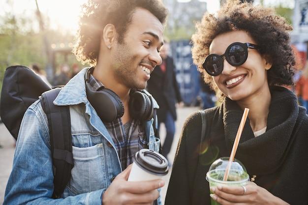 Nahaufnahmeporträt des fröhlichen jungen paares von liebhabern, die getränke halten und einander lächeln, während sie im park gehen und in guter stimmung sind