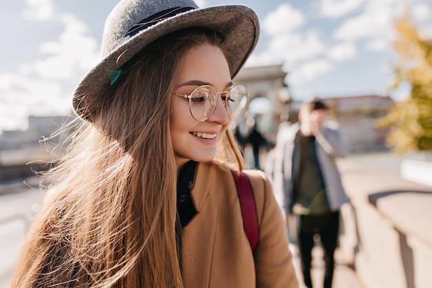 Nahaufnahmeporträt des fröhlichen mädchens mit dem geraden haar, das über straße mit glücklichem gesichtsausdruck geht