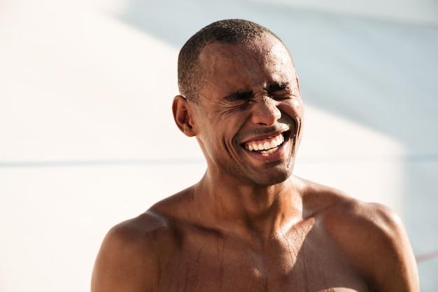 Nahaufnahmeporträt des fröhlichen verschwitzten afrikanischen sportmannes, der nach dem training im stadion kühlt