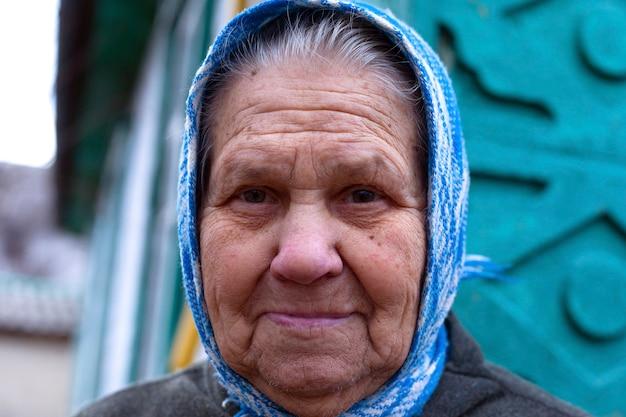 Nahaufnahmeporträt des gesichtes der großmutter in einem kopftuch. alterskonzept.