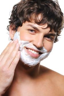 Nahaufnahmeporträt des gesichtes des jungen glücklichen mannes mit rasierschaum