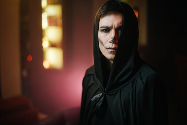 Nahaufnahmeporträt des gesichts eines schönen mannes mit halloween-make-up. junger mann im halloween-kostüm in die kamera schaut