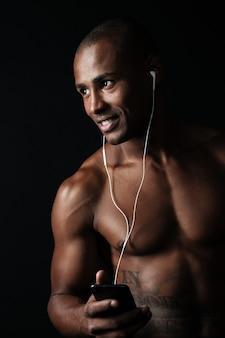 Nahaufnahmeporträt des glücklichen afroamerikanischen sportmannes, der telefon in der hand hält, während musik hören
