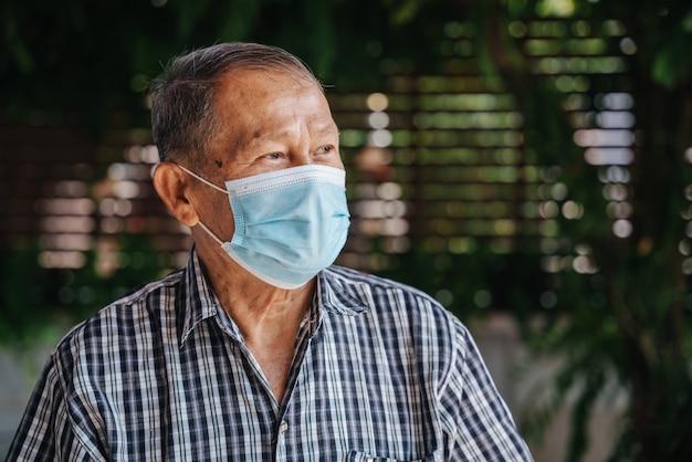Nahaufnahmeporträt des glücklichen asiatischen älteren mannes, der eine maske trägt schauen sie mit hoffnung. alter thailändischer mann