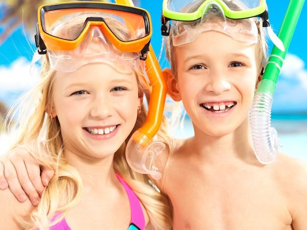 Nahaufnahmeporträt des glücklichen bruders mit schwester, die am strand genießt