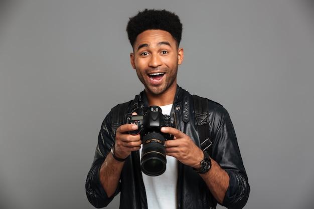 Nahaufnahmeporträt des glücklichen herausgenommenen afroamerikanischen mannes, der photocamera hält