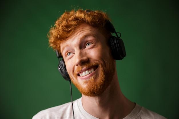 Nahaufnahmeporträt des glücklichen hipster-lesekopfmannes, der musik in kopfhörern hört