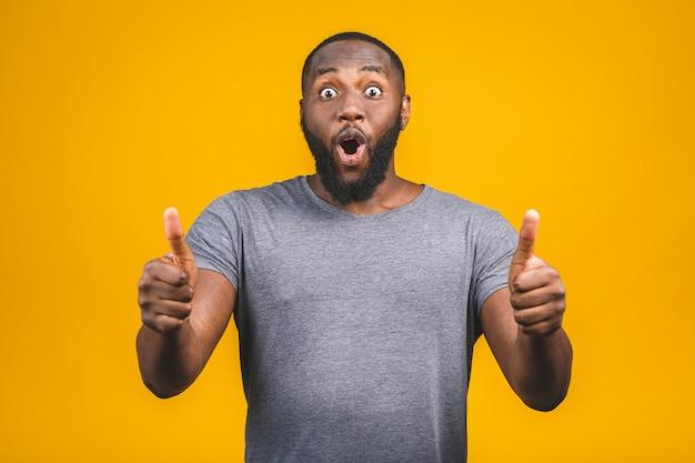 Nahaufnahmeporträt des glücklichen jungen gutaussehenden mannes, der schockiert überraschte offene mundaugen schaut, lokalisiert auf gelber wand. positives menschliches gefühlsgesichtsausdruckgefühl. thombs auf.