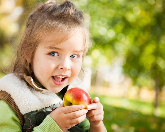 Nahaufnahmeporträt des glücklichen kindes, das im herbst draußen roten apfel isst