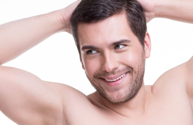 Nahaufnahmeporträt des glücklichen lächelnden jungen mannes mit den händen oben - lokalisiert auf weiß.