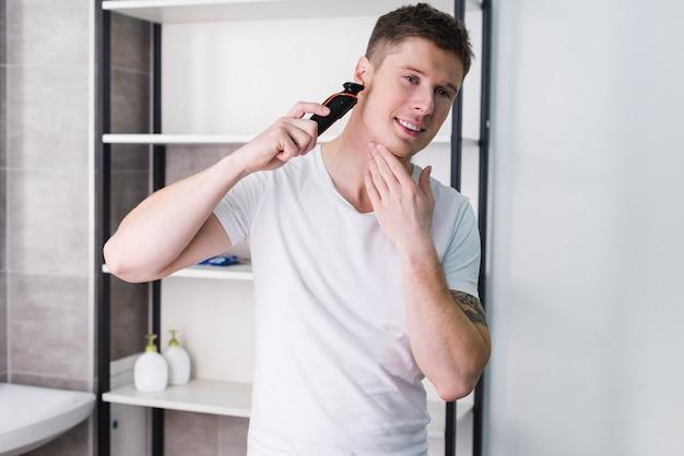 Nahaufnahmeporträt des glücklichen mannes schauend auf kamera und sein gesicht mit elektrorasierer rasierend