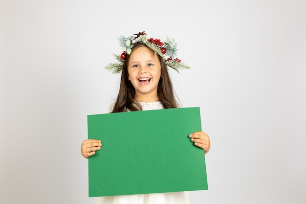 Nahaufnahmeporträt des glücklichen schönen mädchens im weihnachtskranz und im weißen kleid, das grünes leeres ...