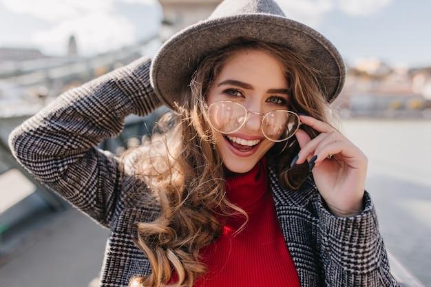 Nahaufnahmeporträt des glückseligen blauäugigen mädchens, das brille berührt und lacht