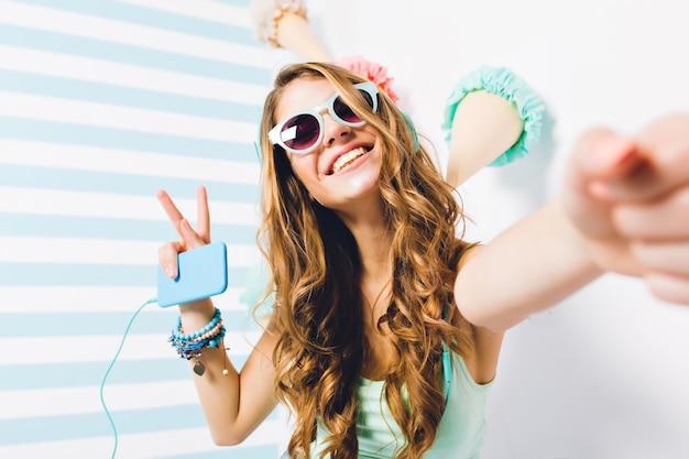 Nahaufnahmeporträt des glückseligen mädchens in der sonnenbrille und in den trendigen armbändern, die mit friedenszeichen aufwerfen. charmante junge frau mit langen haaren, die selfie hält telefon hält und lieblingslied hört.