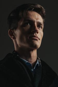 Nahaufnahmeporträt des gutaussehenden mannes auf schwarz