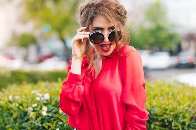 Nahaufnahmeporträt des herrlichen mädchens in der sonnenbrille, die zur kamera im park aufwirft. sie trägt eine rote bluse und eine schöne frisur. sie schaut in die kamera.