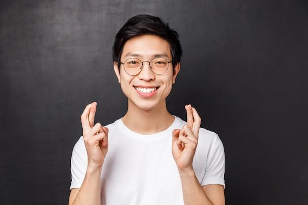 Nahaufnahmeporträt des hoffnungsvollen jungen erwartungsvollen asiatischen kerls, der betet, daumen drückt, viel glück und aufgeregtes lächeln als wunschwunsch, traum wahr werden lassen, schwarze wand flehend stehen