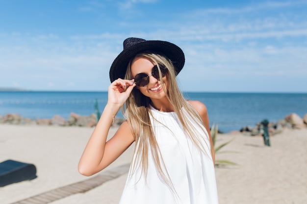 Nahaufnahmeporträt des hübschen blonden mädchens mit langen haaren steht am strand nahe dem meer. sie lächelt in die kamera.