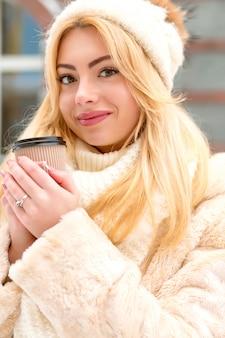 Nahaufnahmeporträt des hübschen blonden modells, das in trendiger winterkleidung gekleidet ist und tee an der straße trinkt