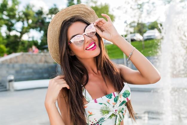 Nahaufnahmeporträt des hübschen brünetten mädchens mit den langen haaren, die zur kamera im park nahe brunnen aufwerfen. sie berührt ihre sonnenbrille und lächelt.