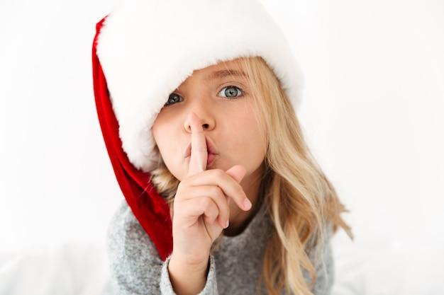 Nahaufnahmeporträt des hübschen kleinen mädchens in der mütze des weihnachtsmanns, das schweigengeste zeigt,