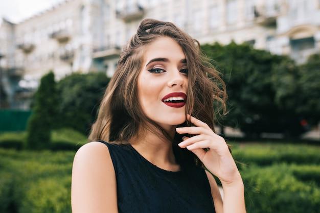 Nahaufnahmeporträt des hübschen mädchens mit dem langen lockigen haar